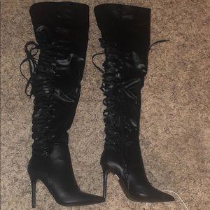 Black tie thigh high boots.